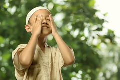 Little asian muslim child in traditional dress praying Stock Image