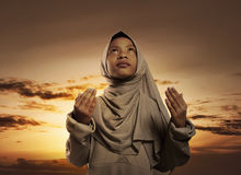 Little asian muslim girl with hijab praying to god. Over sunset background Stock Photo
