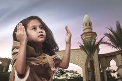 Little asian muslim girl raising hand and praying. With sunset background Stock Photos