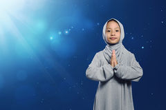 Little asian muslim girl in traditional dress praying Stock Images