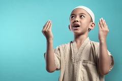 Little asian muslim kid raising hand and praying to god. Over blue background stock images