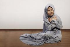 Little asian muslim kid wearing veil praying Stock Photo