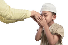 Little asian muslim kid in white cap kissing parents hand. Isolated over white background stock photography