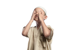 Little asian muslim kid with white cap praying Stock Photos