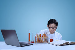 Little asian scientist doing experiment. Cute little scientist wearing lab coat doing experiment Stock Photos
