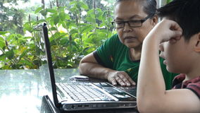 Little asian Senior woman and young boy with laptop computer . Little asian Senior woman and young boy are playing laptop computer stock video
