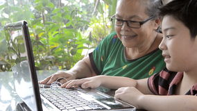 Little asian Senior woman and young boy with laptop computer . stock video