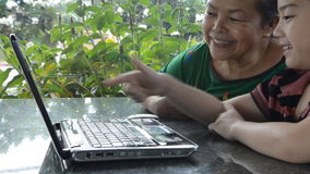 Little asian Senior woman and young boy with laptop computer . Little asian Senior woman and young boy are playing laptop computer stock video footage