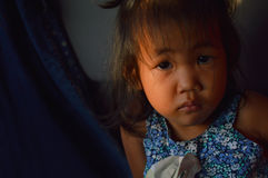 Little asian shy girl child 4 years old angry and sad looks at the camera. Her dress is blu Royalty Free Stock Photography