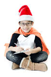 Little asian smile boy with santa hat. Little asian cute boy with santa hat playing supper hero sign isolated on white background Royalty Free Stock Images