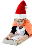 Little asian smile boy with santa hat. Playing tablet isolated on white background Stock Image