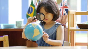 Little Asian student looking at globe. With magnifying glass stock video