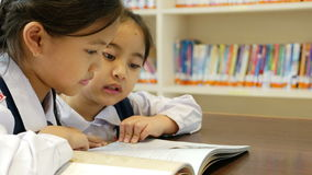 Little Asian students wearing uniforms and reading book in library stock footage