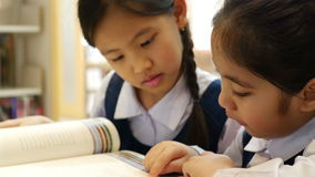 Little Asian students wearing uniforms and reading book in library stock video footage