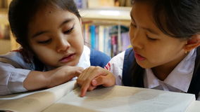 Little Asian students wearing uniforms and reading book in library stock video