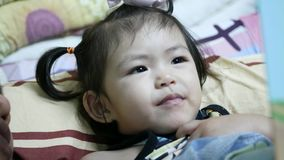 Little Asian, Thai, baby girl, 2 years old, repeating aloud after her mother a vocabulary from a book, before her bedtime. Video clip with audio stock video