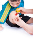 Little asian (thai) boy looking wound his leg. Nurse provides first aid, shoot in studio, Isolated on white background Stock Photo