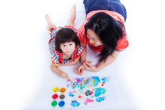 Little asian (thai) girl painting with her mother near by, on wh Royalty Free Stock Photos
