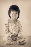 Little asian (thai) girl sitting. Vintage and retro picture styl Stock Photo