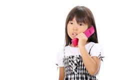 Little asiatisk flicka som kallar vid telefonen Royaltyfri Foto