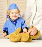 Little assistant examines teddy bear. Male hand holds bear. And boy in medical gown holds stethoscope on wooden background. Kid with happy face plays doctor stock photo