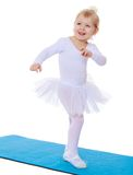Little athlete in a white suit jumping on the mat Royalty Free Stock Photography