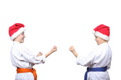 Little athletes in caps of Santa Claus are standing in rack of karate Stock Images