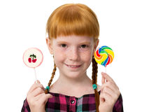 Little attractive redheaded girl with freckles holding colorful candy Stock Photos