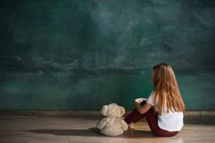 Little girl with teddy bear sitting on floor in empty room. Autism concept. Little autistic girl with teddy bear sitting on floor at empty room. Autism concept Stock Images