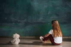 Little girl with teddy bear sitting on floor in empty room. Autism concept. Little autistic girl with teddy bear sitting on floor at empty room. Autism concept Stock Image