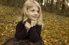 Little Autumn Girl. Cute little girl, posing on a tree stump in autumn Stock Image