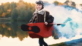 Little aviator girl running at sunset lake in fun cardboard plane with blue colour smoke playing a pilot slow motion.