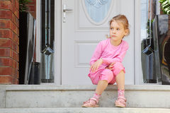 Little Awake Girl Sits On Stairs Royalty Free Stock Image