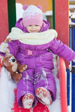 Little babe girl playing on the winter playground. Royalty Free Stock Photography
