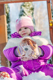 Little babe girl playing on the winter playground. Stock Image