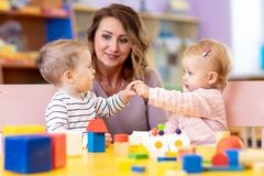 Little babies playing with Montessori toy in pre-school, creche or kindergarten