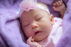 Little baby is asleep on the purple bed., Healthcare. Little baby is asleep on the purple bed Royalty Free Stock Photos