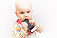 Little baby baby chews on a mobile phone Stock Photos