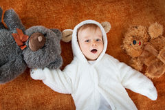 Little baby in bear costume with plush toys Stock Images