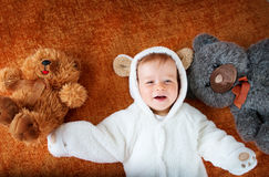Little baby in bear costume with plush toys Royalty Free Stock Images