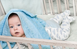 Little baby in bed hidden in a towel Stock Image