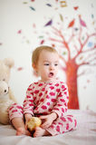 Little baby in bed wearing red pyjamas Royalty Free Stock Photo