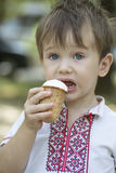 Little baby with big blue eyes eats ice cream Stock Images
