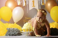 Little baby birthday one year girl crushing her yellow cake royalty free stock image
