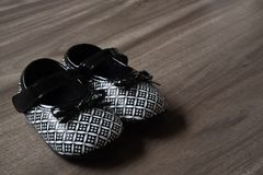 Little Baby black and White Children Shoes on wooden Background. Little Baby black and White Children Shoes on wood Background stock image