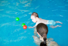 Little baby with blue eyes learning to swim. With her mother stock images