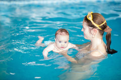 Little baby with blue eyes learning to swim. With her mother Royalty Free Stock Photography