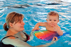 Little baby with blue eyes learning to swim Royalty Free Stock Images
