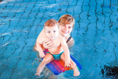 Little baby with blue eyes learning to swim Stock Photo