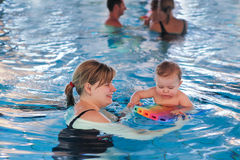 Little baby with blue eyes learning to swim Royalty Free Stock Photography